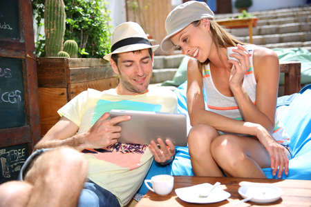 Young couple on holidays connected to internet with tablet photo