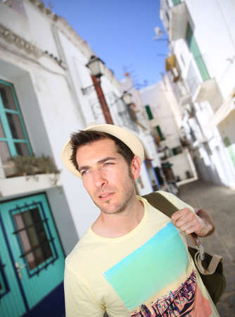 Man with backpack visiting Ibiza town Stock Photo