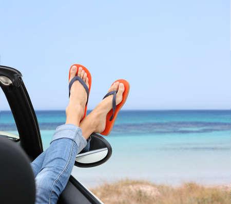 Primer plano de los pies de la mujer por la ventana del coche convertible Foto de archivo