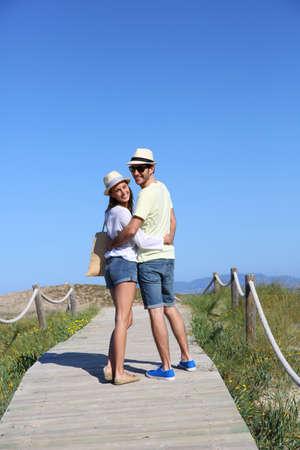 Couple walking on dunes wooden pontoon photo