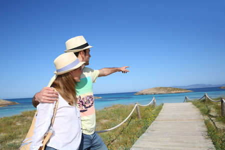 Couple of tourists admiring view from Formentera Island photo