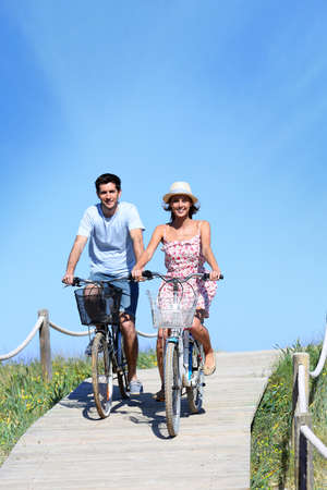 Couple riding bicycles in summertime photo