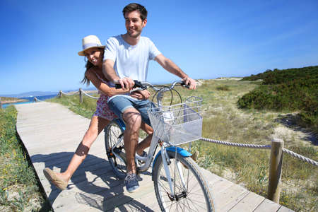 Man giving bike ride to girlfriend on beautiful Island photo