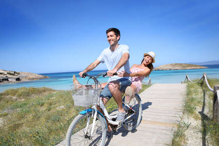 formentera: Man giving bike ride to girlfriend on beautiful Island Stock Photo