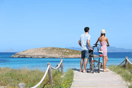 Couple standing by gorgeous beach with bicycles photo