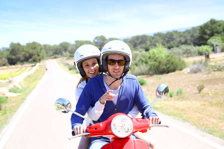 casco de moto: Pareja alegre que monta moto roja en la isla
