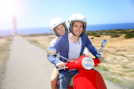 Cheerful couple riding red moto on island Imagens