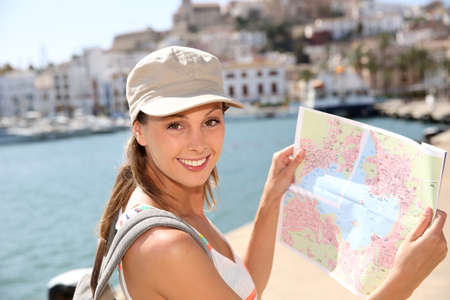 Cheerful tourist girl looking at city map