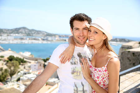 Happy couple of tourists visiting Ibiza island in summer photo