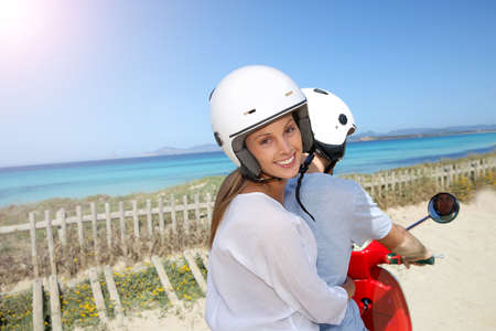 Cheerful girl riding moto with boyfriend by the beach photo