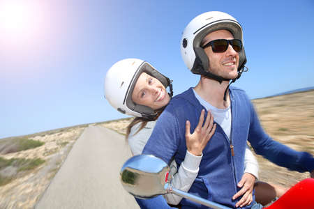 Cheerful couple riding red moto on island photo