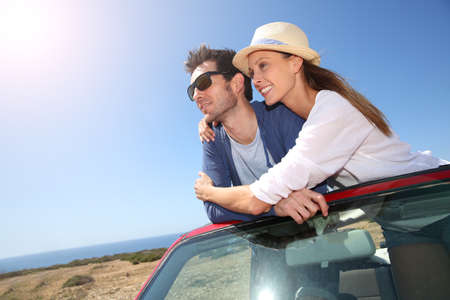 Couple enjoying view from top of convertible car photo