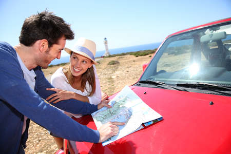 Couple looking at road map on red car hood photo