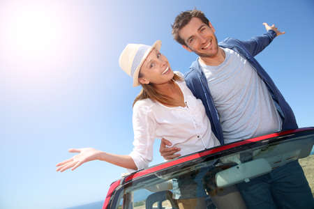 funny car: Funny couple with arms up from convertible car