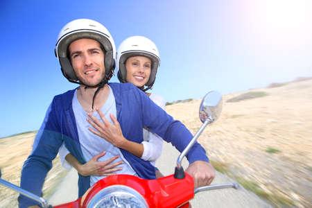 vespa: Pareja alegre que monta moto roja en la isla