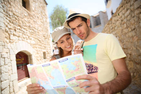 Couple of tourists in the street reading city map photo