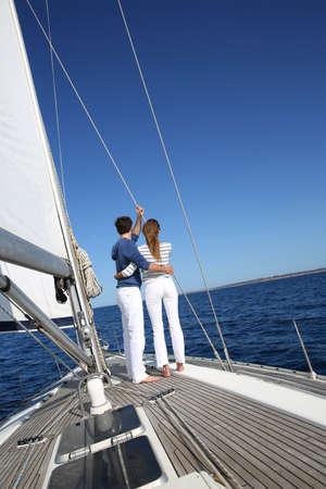 Fancy couple enjoying sailing on a beautiful sailboat photo