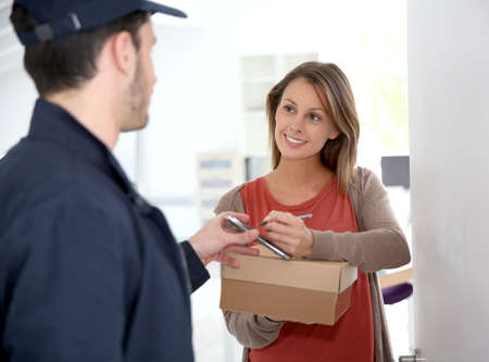 job opening: Woman sigining electronic receipt of delivered package