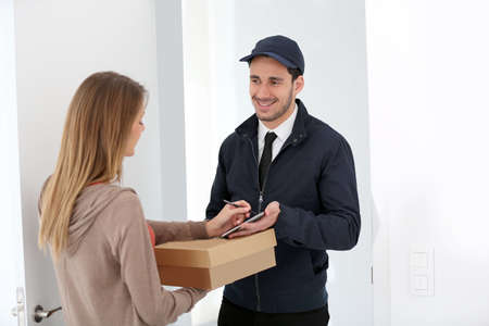 Woman signing receipt of package delivery Standard-Bild