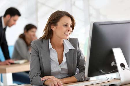 ordinateur de bureau: Femme d'affaires travaillant sur ordinateur de bureau