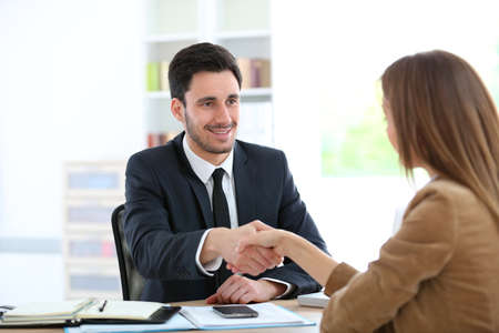 client meeting: Woman giving handshake to financial adviser Stock Photo