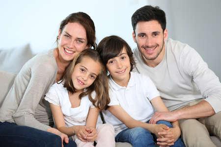 Gelukkige familie zitten samen in de bank Stockfoto