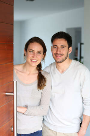 Happy couple opening new home entrance door photo