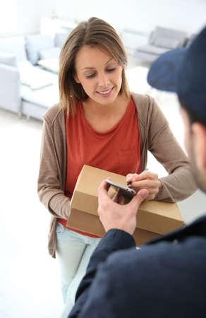 Vrouw sigining elektronische ontvangst van geleverde pakket