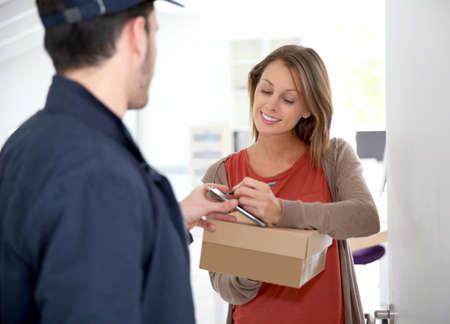 Mujer sigining recepción electrónica de paquete entregado