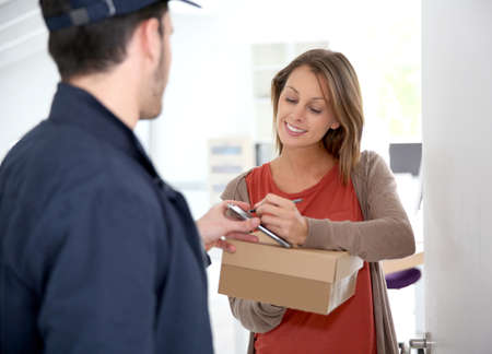 package shipment: Woman sigining electronic receipt of delivered package
