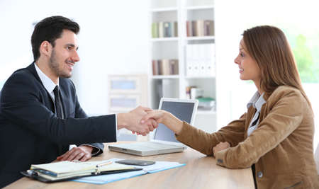 Woman giving handshake to financial adviser Stock Photo