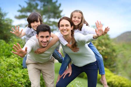 house outside: Happy family having fun in home garden Stock Photo