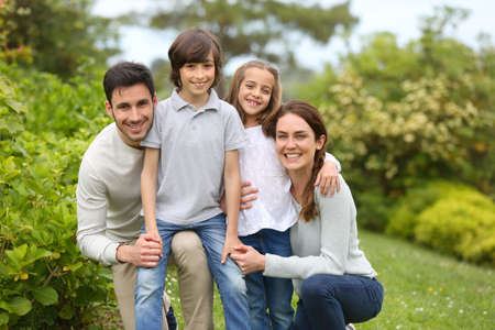 Portrait of cheerful family standing in home garden Stock Photo