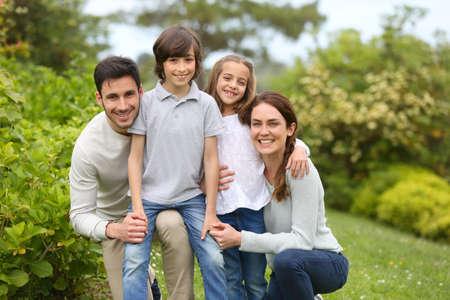 Retrato de família alegre em pé na horta Imagens