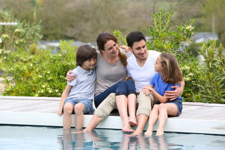 Parents with children relaxing by the pool photo