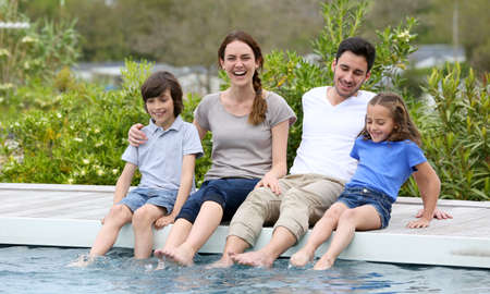 european people: Parents with children relaxing by the pool