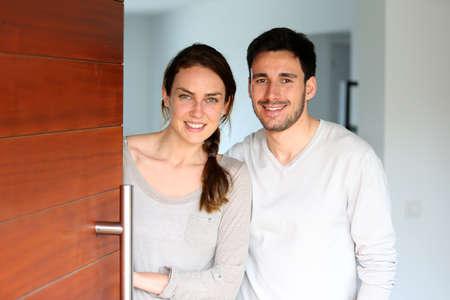 Happy couple opening new home entrance door photo