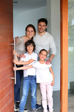 Family happy to welcome people in brand new home Archivio Fotografico
