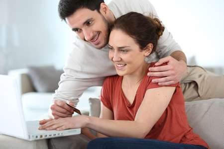 secured payment: Couple at home shopping online with laptop