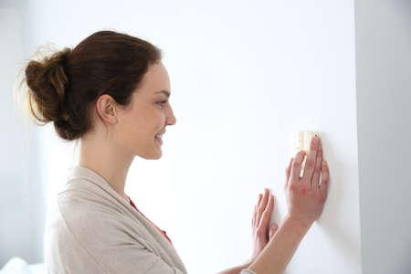 Vrouw programmering temperatuur in huis Stockfoto