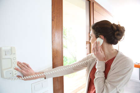 Woman inside home answering security phone photo