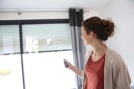 Mulher usando o controle remoto para abrir o obturador elétrico