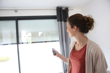 shutter: Woman using remote control to open electric shutter Stock Photo