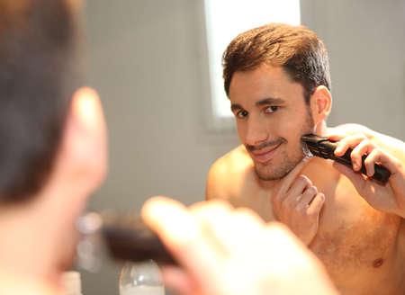 shaver: Man using electric shaver in bathroom