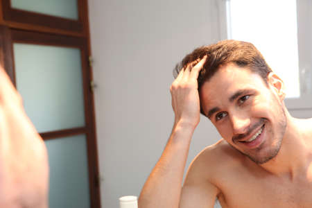 Homem novo que olha o cabelo no espelho