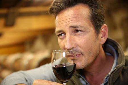 winemaker: Winemaker tasting red wine in cellar Stock Photo