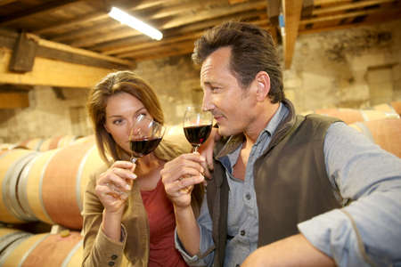 Oenologists in wine cellar tasting red wine photo