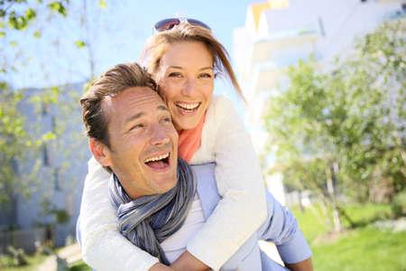 parejas enamoradas: Hombre dando caballito a la mujer en la ciudad Foto de archivo