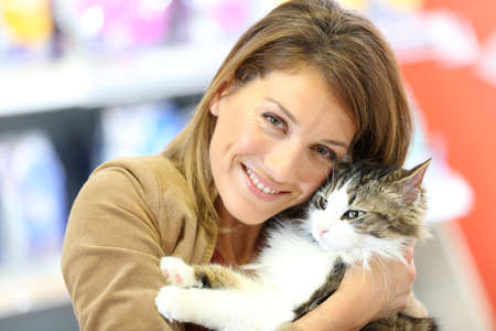 Portrait of smiling woman holding cat  photo