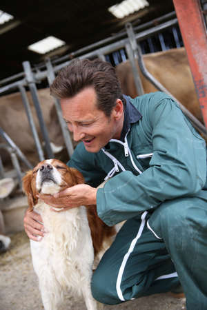 Breeder petting dog outside the barn photo